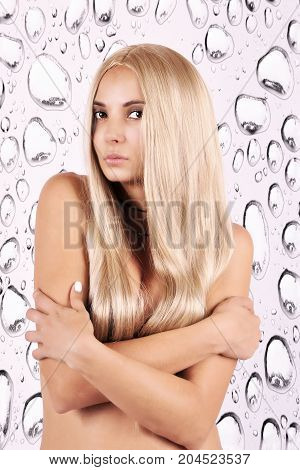 naked girl with long blond hair crossed her arms over her chest on an abstract background