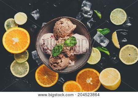 Portion of assorted ice cream scoops in bowl with ice cubes, lemon and orange slices and mint on black background top view. Delicious cold sweet dessert, close up