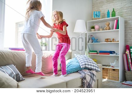 Cute fair-haired little sisters holding hands and jumping on cozy sofa while spending weekend together at spacious living room