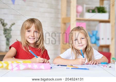 Group portrait of cute little sisters looking at camera with wide smiles while drawing pictures with felt-tip pens, interior of cozy bedroom on background