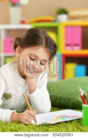 Portrait of a cute girl drawing at home