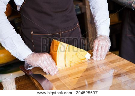 Shop assistant wrapping a piece of cheese. Packing order at grocery shop in cling film on wooden table, background