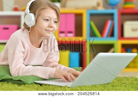 Cute little girl in headphones using laptop