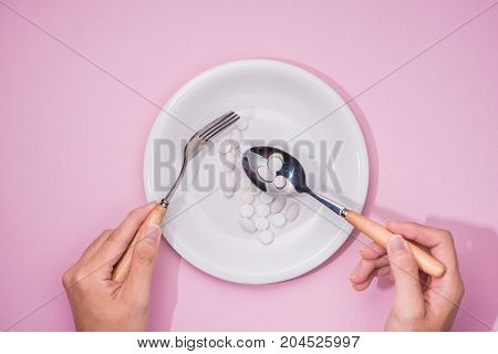 Top View Of Man's Hands At Dining Table Holding A Fork And Knife Above Dish With Pills Over Pink Bac
