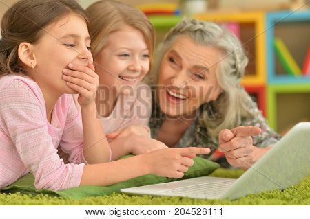 senior woman with granddaughters using laptop while lying on floor
