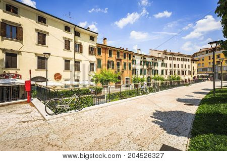 VERONA ITALY - JUNE 25 2016: Picture from Piazza Cittadella with restaurants trees and bikes in a sunny day with clouds. Verona Italy.