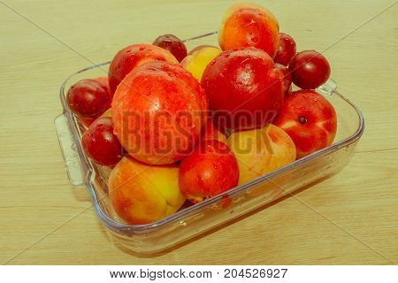 Fresh juicy peaches nectarine and plums on the kitchen table. fruit on the table - Retro color