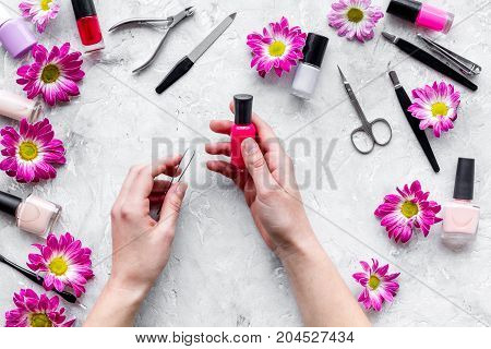 Choose nail polish for manicure. Woman hand hold bottle of polish on grey background top view.