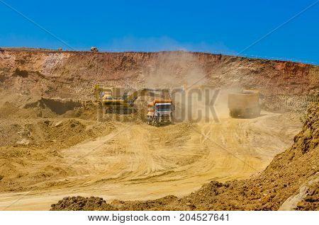 excavator and trucks working in the quarry mining