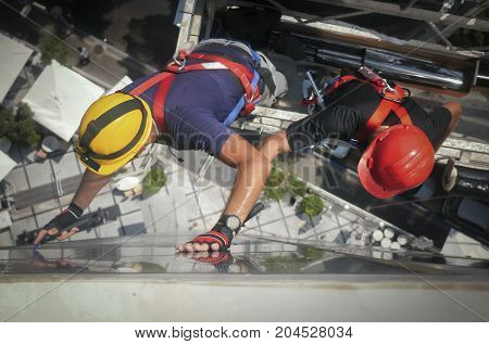 Two workmen on a suspended platform or cage hanging against the exterior of a high-rise building viewed from above looking down on their hardhats