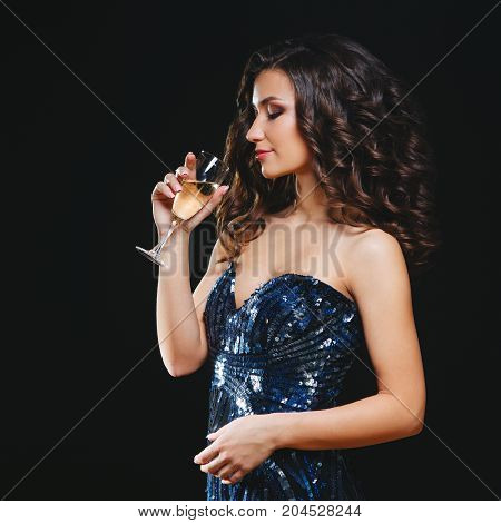 Celebrating Woman. Holiday People. Beautiful Girl with Makeup Holding Glass of Champagne. Dark background