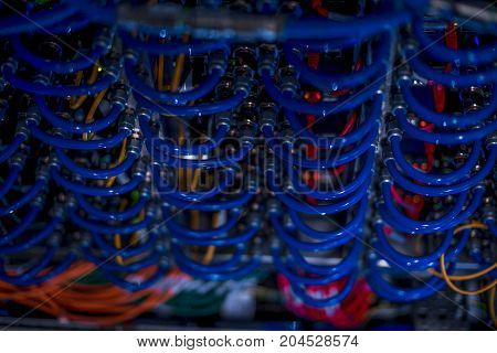 Background image of blue wires connecting blade servers in cabinet of supercomputer, close up