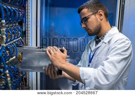 Side view portrait of young man in lab coat taking out blade server out of cabinet while working with supercomputer