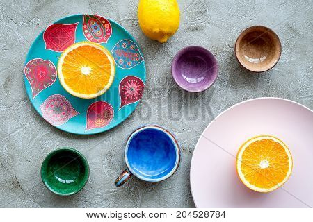 Crockery pattern. Cups and plates near tropical leaves and fruits on grey background top view.