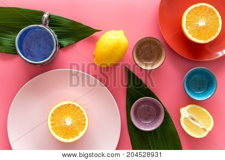 Crockery pattern. Cups and plates near tropical leaves and fruits on pink background top view.