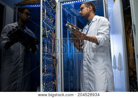 Low angle portrait of young man wearing lab coat checking blade servers while working with supercomputer for scientific purposes