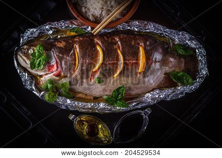 Trout baked with herbs and lemon slices in foil on an old dark baking sheet served with sauces and rice