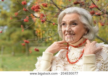 senior beautiful   woman  with lace from berries posing outdoors