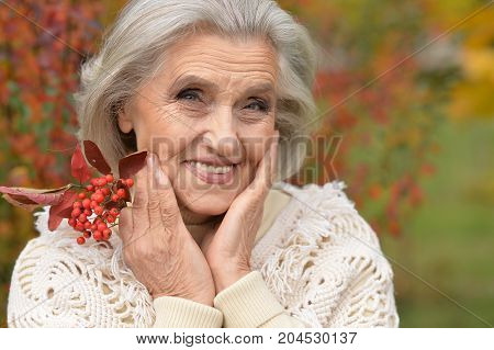 Portrait of senior beautiful woman posing with berries