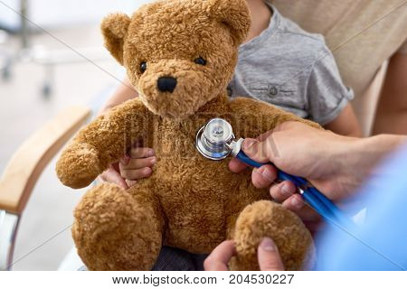 Close-up shot of unrecognizable doctor using stethoscope in order to examine teddy bear belonging to little patient