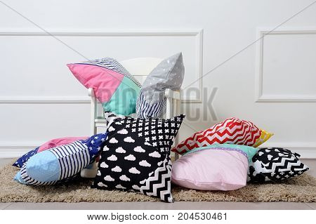 A Lot Of Pillows Lying Next To The Rocking Chair