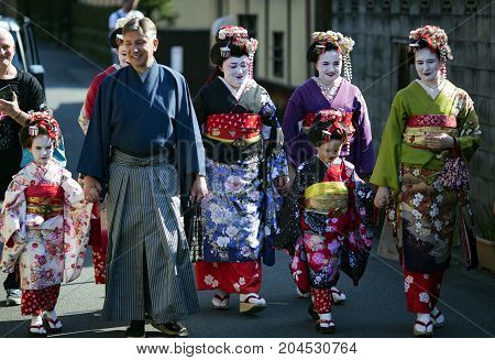 JAPAN, KYOTO, APRIL, 05, 2017 -  Four nice woman, two children and a man in national Japanese clothes walk down the street at old-fashioned town of Gion district, Kyoto Japan.