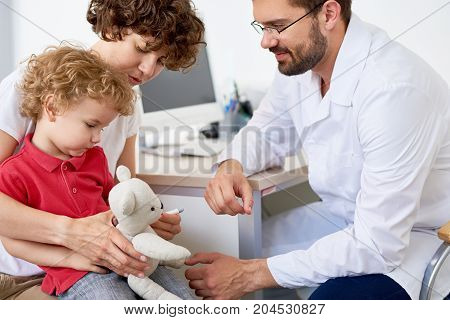 Profile view of handsome bearded doctor taking temperature of teddy bear while examining curly little boy sitting on laps of his pretty mother