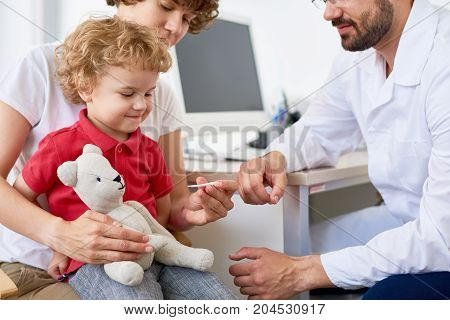 Pretty middle-aged mother checking temperature of her curly little son while having consultation at pediatrician office