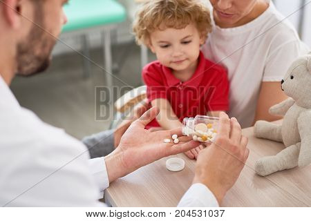 Confident young pediatrician giving pills to little patient after conducted check-up, interior of modern office on background