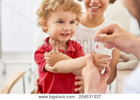 Waist-up portrait of smiling little boy showing thumb up while pediatrician putting bandage on injured finger, blurred background