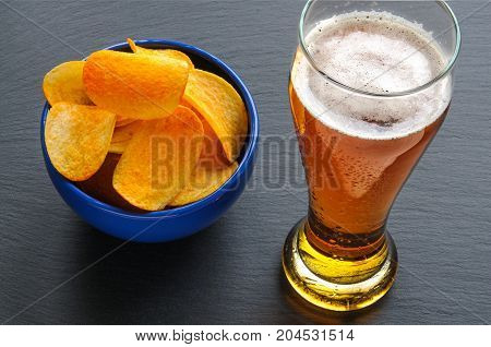 Beer and many yellow saddle chips. Above view