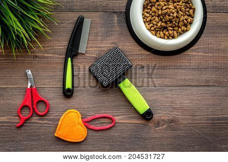 grooming equipment with brushes for care and training pet on wooden desk background top view