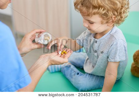 Unrecognizable pediatrician giving vitamins to curly little patient after completion of check-up, blurred background