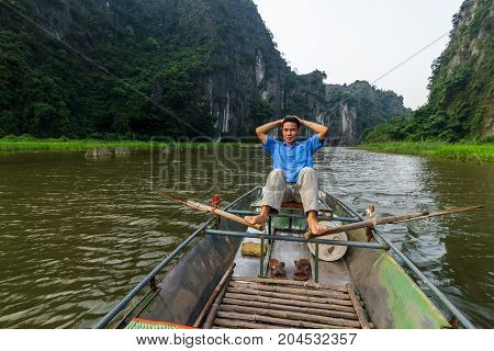 A Tour Guide Paddles A Boat Along The Ngo Dong River At Trang An Unesco World Heritage Site In Ninh