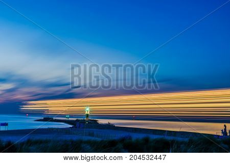 night view of lighthouse of Warnemunde on the Baltic Sea at the harbor with light stripes from ship , Germany Rostock