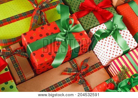 Pretty gift wrapping background top view. Lots of gift boxes in stylish modern colored paper, decorated with red, green satin ribbon bows.