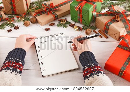 Women hands with notebook and pen. Creative presents in craft and colored paper decorated for any holiday concept, with copy space on notebook. Red, green ribbons for christmas. Point of view, crop