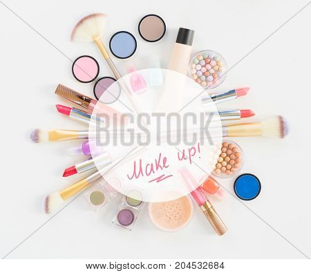 Colorful make up and brushes flat lay scene on white background with copy space