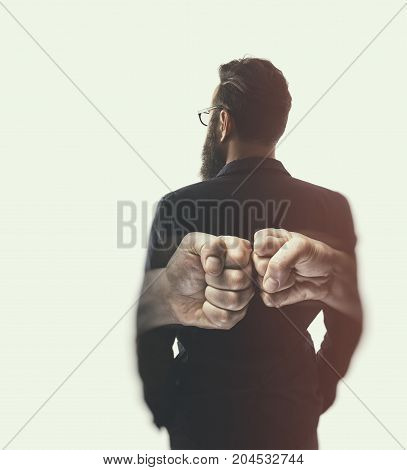 Double exposure image. Silhouette of a man in a business suit are combined with a picture of fists. Concept of confrontation competition etc.