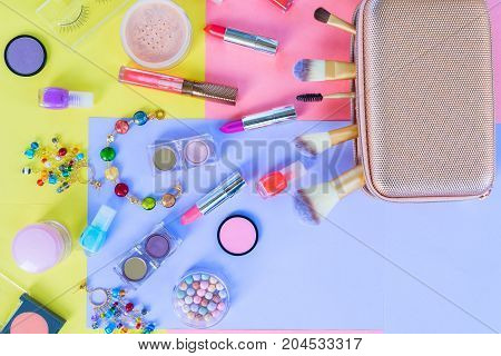 Colorful make up products material design flat lay scene with falling from handbag