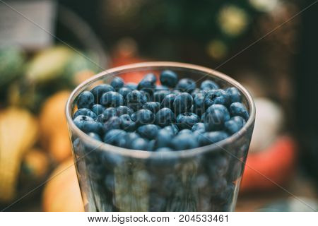 Close-up view of glass with fresh raw bog whortleberry or bilberry just recently harvested for Thanksgiven day with colorful spots of defocused vegetables in background; shallow depth of field