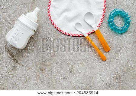 Mother care breast milk in bottle and infant formula powdered healthy food with bib for baby feeding on stone table background top view mock up