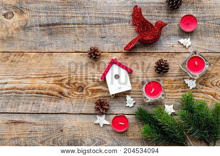 New Year decorations with bird, house toys and christmas tree branche on wooden table background top veiw mock up