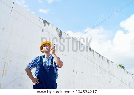 Waist-up portrait of confident young construction worker wearing hardhat and overall looking away while talking via walkie-talkie, wall of unfinished building on background