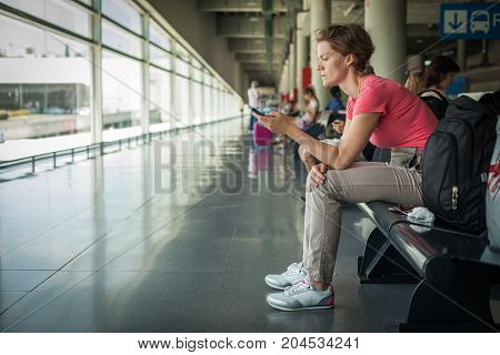 Young Woman With Mobile Phone Waiting For A Bus At The Station