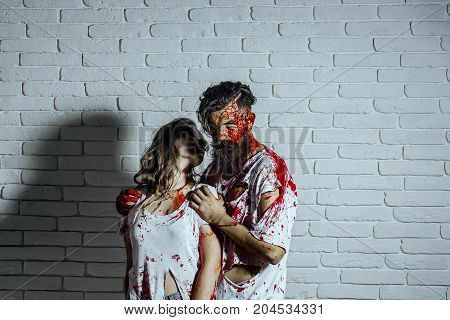 Halloween couple in love on white brick wall. Woman and man in bloody torn clothes. Two vampires bleeding with red blood. Bearded hipster hugging girl in eyeglasses. Halloween holiday concept