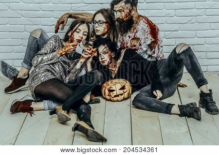 Halloween girl vampire applying lip gloss makeup. Bearded man with bloody pumpkin and axe. Women with red blood splatters. Halloween holiday celebration concept. Friends relaxing on wooden floor.