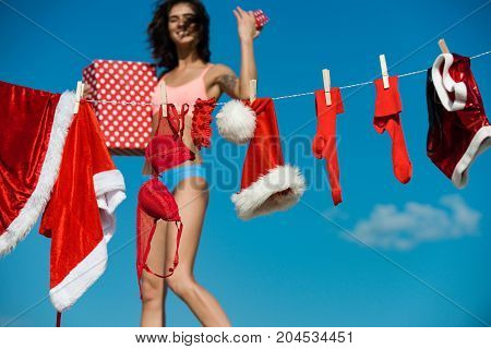 Santa claus girl hanging clothes for drying. Christmas woman with happy face outdoor. Laundry and dry cleaning. New year girl on sunny blue sky. Xmas red costume on rope with pin.