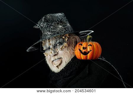 halloween man scary pumpkin and thorns on face in hat on black background
