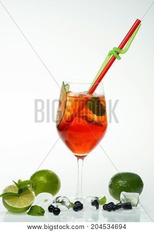 Cocktail with blueberry isolated on white background. Party and summer vacation. Alcoholic beverage and currant berry at restaurant. Drink and food. Drinking straw in cocktail glass with lime at bar.